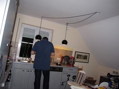Manden hænger lamper op...